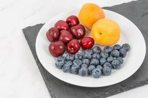 Blueberries Apricots and Cherries served on the plate