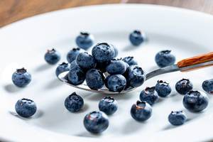 Blueberries in a spoon and scattered on a white plate (Flip 2019)
