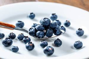 Blueberries in a spoon and scattered on a white plate