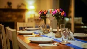 Blumen in Vase dienen als Tischdekoration auf gedecktem Esstisch