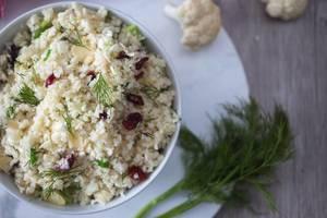 Blumenkohl-Reis mit Mandeln und Cranberries in einer Schale in der Aifsicht mit Blumenkohl und Dill im Hintergrund