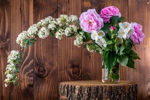 Blumenstrauß mit verschiednen Rosa und weißen Blumen, in einer Glasvase auf einem dekorativen Baumstamm