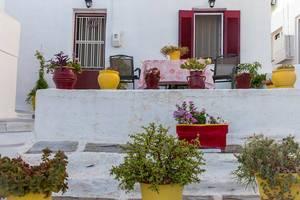Blumentöpfe und Pflanzen auf einer Veranda eines landestypischen Kalksteinhauses in der Hafenstadt Naoussa, Griechenland