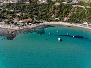 Boats, beach and hill with hotels in Afitos, Greece