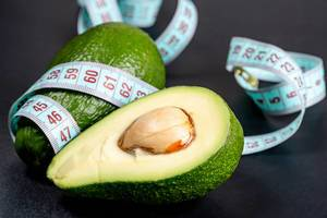 Body care and proper nutrition. Fresh avocado and measuring tape on black