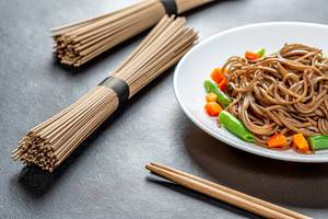 Boiled and raw buckwheat soba noodles on a black background