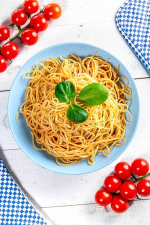Boiled spaghetti with cherry tomatoes on a white wooden table. Top view (Flip 2019)