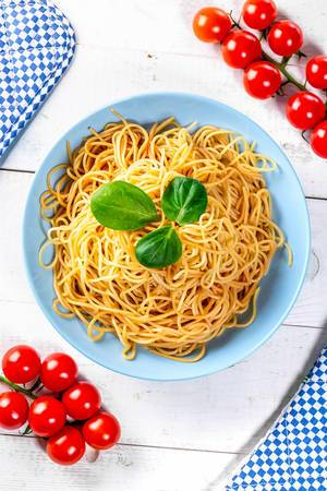 Boiled spaghetti with cherry tomatoes on a white wooden table. Top view