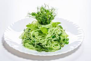Boiled spaghetti with fresh pea sprouts and young peas on a white plate