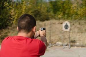 Bokeh eines Schützen der mit einer Pistole auf eine Zielscheieb schießt
