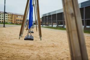 Bokeh Foto von einer Schaukel auf einem Spielplatz mit Sandboden