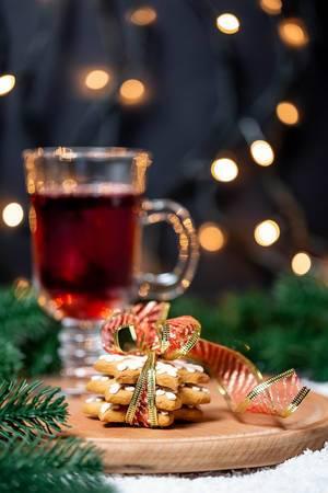 Bokeh mit Zimtsternen gestapelt mit Schleife und einem Glas Glühwein im Hintergrund