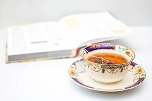 Bokeh of full Cup of Tea with open Book in the background