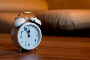 Bokeh Photo of Alarm Clock standing on a Bedroom Table next to the Bed