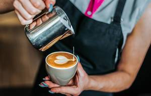 Bokeh Photo of Barista making a Latte Heart Design on a Small Cup of Coffee