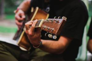 Bokeh Photo of Musician playing Acoustic Guitar