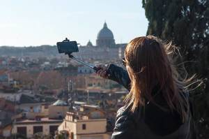 Bokeh Photo of Person taking Selfie with Selfie Stick with St. Peter