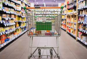 Bokeh Rear View Photo of Shopping Cart standing in empty Grocery Store Aisle