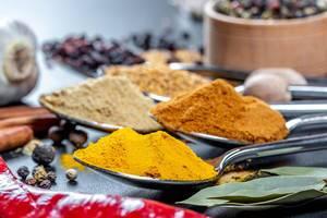 Bokeh von Gewürzpulvern auf Löffeln - Kurkuma, Curry, Knoblauch