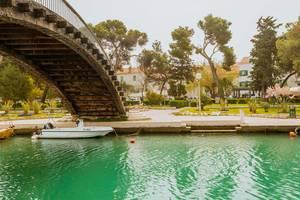 Boot liegt auf unter einer Brücke in Trogir