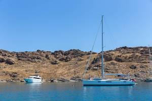 Boote legen in der Bucht vor Kolimpithres, Paros - Griechenland, an und Urlauber schwimmen vor der felsigen Küste im Mittelmeer