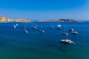 Boote und Katamarane liegen auf dem blauen Wasser der Ägäis, vor dem Peperistrand von Naousa in Griechenland