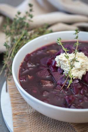 Borschtsch Suppe aus Rotkohl, Suppenfleisch und Kartoffeln dekoriert mit Rosmarin in weißer Schüssel