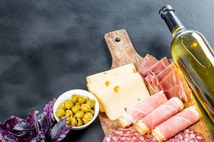 Bottle of white wine, fresh Basil, cold cuts, cheese with green pickled olives on black background (Flip 2019)