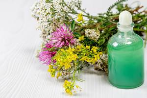 Bottle with green cosmetic and a bouquet of wild flowers on a white wooden background. The concept of natural cosmetics (Flip 2019)