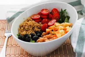 Bouddha Bowl mit Quinoa, Tomaten, Linsen, Oliven und Kürbis