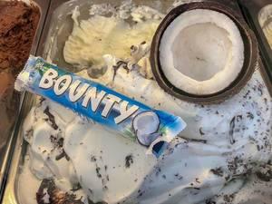 Bounty Kokosnuss Eis mit einer halben Kokosnuss und einem Bounty Schokoriegel