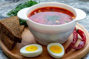 Bowl of beetroot soup borsch with egg, pepper and slices of black bread (Flip 2019)
