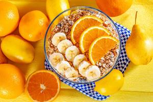 Bowl of cereal with bananas and oranges for Breakfast on fresh fruit background