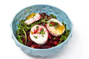 Bowl of lettuce beetroot, whole rucola leaves and poached eggs with white background