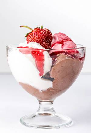 Bowl with ice cream and strawberries on white background
