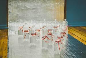 Bowling-Spiel mit Wasserflaschen, die mit  rotem Geschenkband verziert sind auf silberner Bahn
