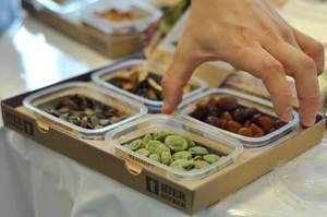 Box with dried fruit, pumpkin seeds and wasabi peanuts