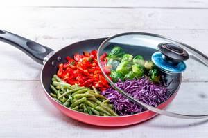 Bratpfanne mit geschnittenem Gemüse auf weißem Holztisch