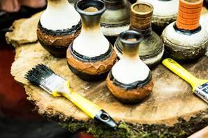 Braun, schwarz und weiß bemalte Tonvasen mit zwei gelben Pinseln auf Tisch aus Baumstamm