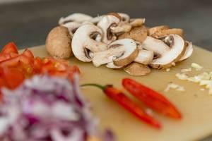 Braune Champignons in Scheiben - Bokeh mit Chili und Zwiebeln im Vordergrund