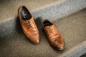 Braune, lederne Schuhe des Bräutigams stehen auf mit Teppich überzogener Treppe