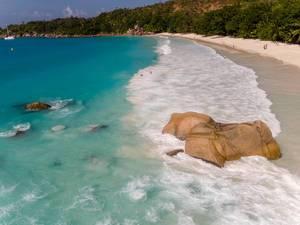Brauner Granitstein umgeben von den Wellen des Indischen Ozeans an der Nordküste Anse Lazio mit Touristen im Hintergrund auf Praslin, Seychellen