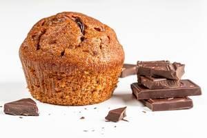 Brauner Muffin mit Schokoladenstücken vor weißem Hintergrund