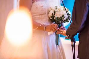 Braut in weißem Kleid hält Brautstrauß und steckt zukünftigem Ehemann den Ehering an