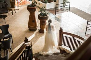 Braut in weißem Kleid und mit Schleier schreitet Holztreppe hinunter in Halle des Zaycoland Hotels