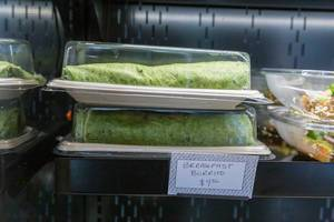 Breakfast Burrito with green tortilla served in a plastic tray to go at For Five Coffee Roasters in Chicago