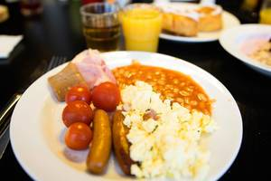 Breakfast plate with eggs, sausages, beans, and tomatoes (Flip 2019)