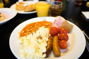 Breakfast plate with eggs, sausages, beans, and tomatoes