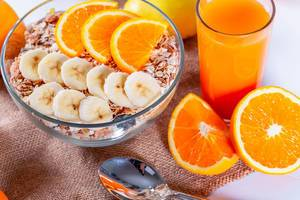 Breakfast with porridge and fruit orange and banana with a glass of fresh juice on the background of burlap