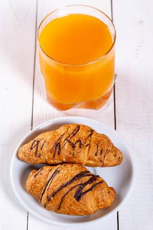 Breakfast with two croissants and fresh juice
